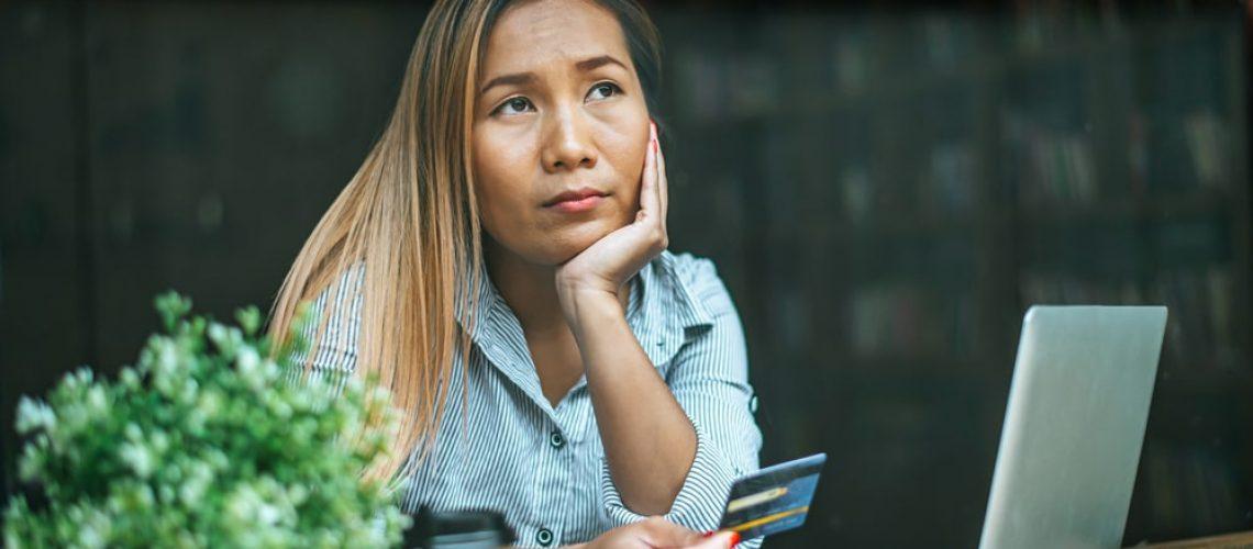 woman-sitting-thinking-about-credit-card-balances-4LDH36F-1